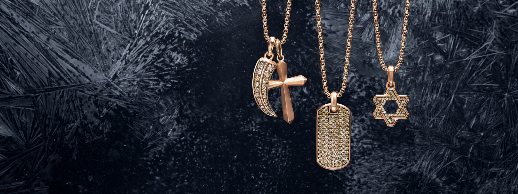 A color photograph shows three David Yurman men's box-chain necklaces in 18K rose gold arranged in a row atop a dark, scratched, snow-dusted icy surface. Each necklace is strung with one or two David Yurman men's amulets crafted from 18K rose gold. From left is a Roman claw with pavé cognac diamonds, a Roman cross, a Pavé tag with pavé cognac diamonds, and a Deco Star of David with pavé cognac diamonds.