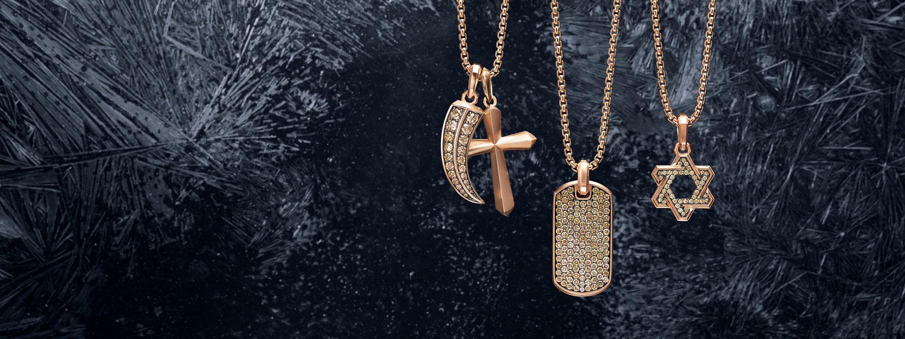 一张彩色照片展示了三条David Yurman男士箱纹链项链,采用18K玫瑰金材质,排成一排,置于深色带划痕的积雪冰面上。每条项链上均悬挂一个或两个David Yurman男士护身符,采用18K玫瑰金。左起为密镶干邑色钻石Roman爪、Roman十字架、密镶干邑色钻石的吊牌以及密镶干邑色钻石的Deco Star of David。