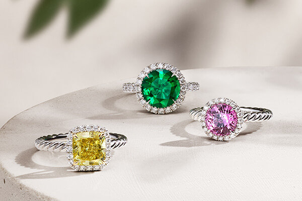 Three DY Capri® rings, in platinum with diamonds and a DY Signature Cut™ yellow diamond, emerald or pink sapphire center stone, in a group on a beige stone and casting long shadows.