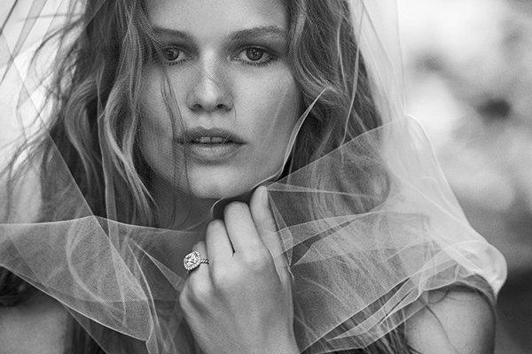 模特Anna Ewers戴着白色面纱和DY Capri铂金钻石订婚戒指的黑白照片。