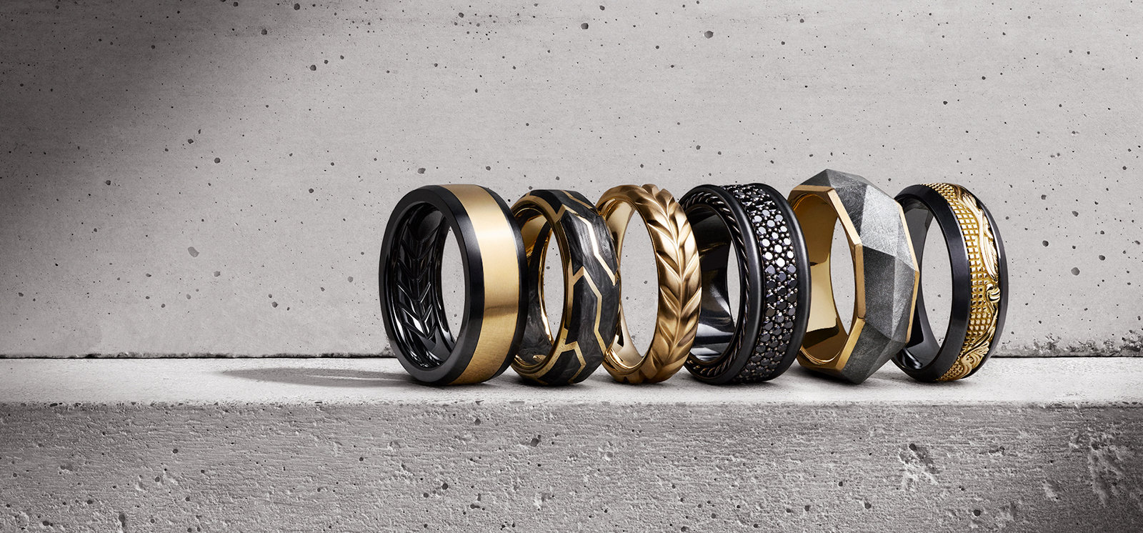 David Yurman Beveled, Forged Carbon, Chevron, Streamline®, Faceted and Waves bands with or in 18K yellow gold and black titanium, forged carbon, black diamonds or meteorite, in a row in a ray of light on a white stone.