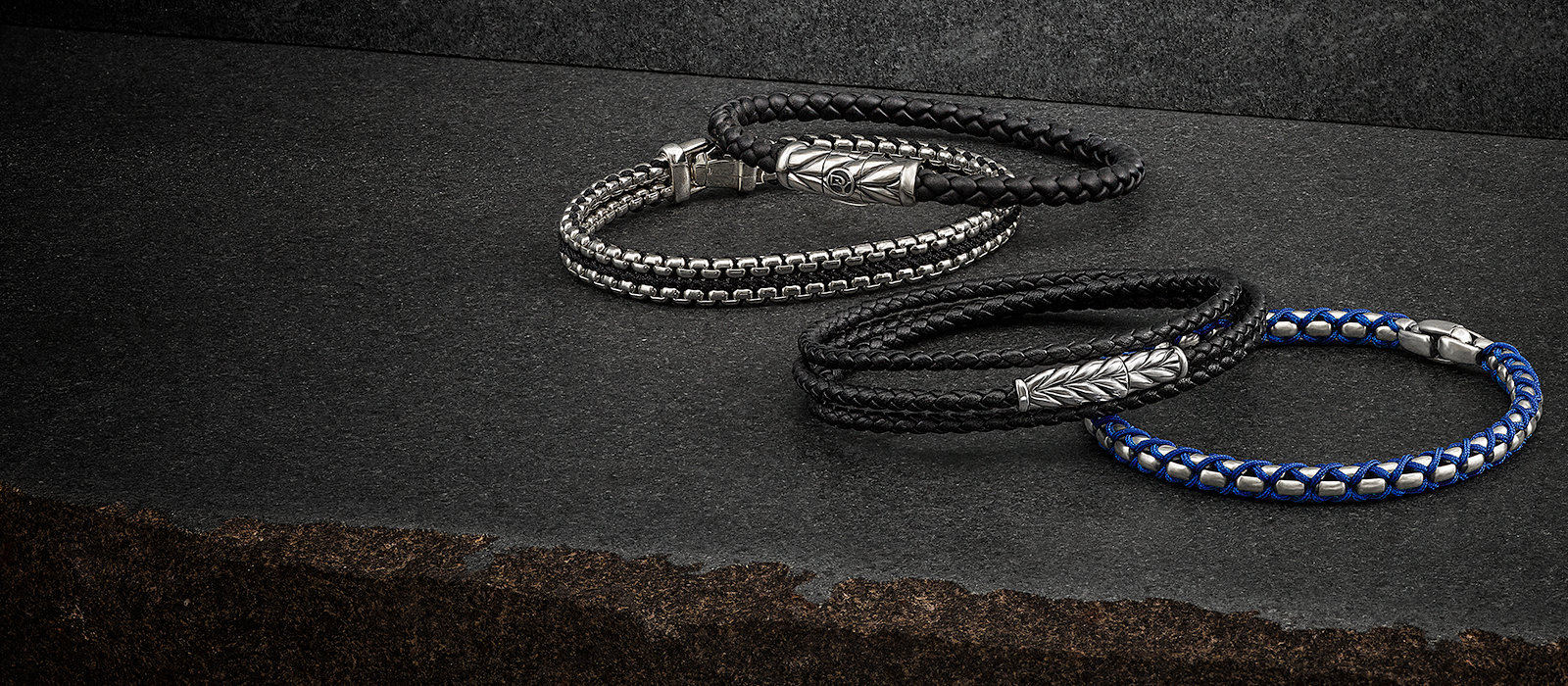 Woven Box Chain bracelet in sterling silver and black nylon, Chevron black rubber-weave and black leather triple-wrap bracelets with sterling silver and Woven Box Chain bracelet in sterling silver with blue nylon on a stone.