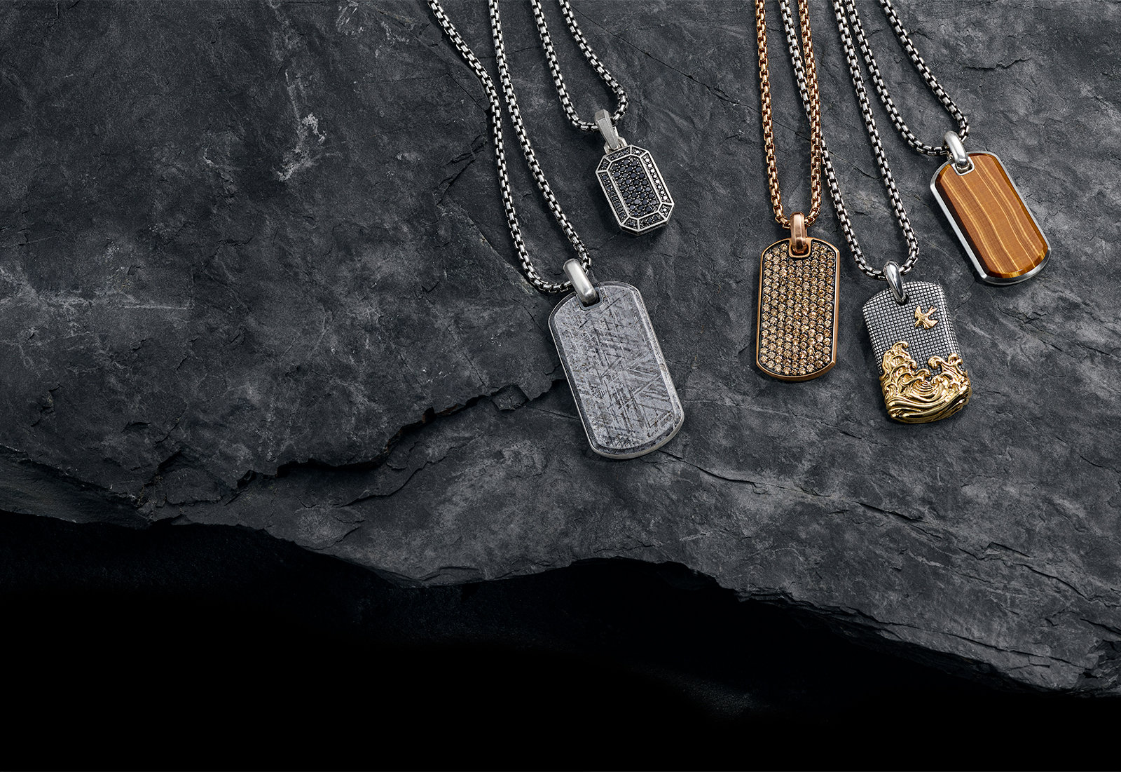 David Yurman Meteorite, Pavé, Waves and Exotic Stone tags in sterling silver with meteorite, pavé black diamonds, 18K yellow gold and cat's eye, or in 18K rose gold with cognac diamonds against a stone.
