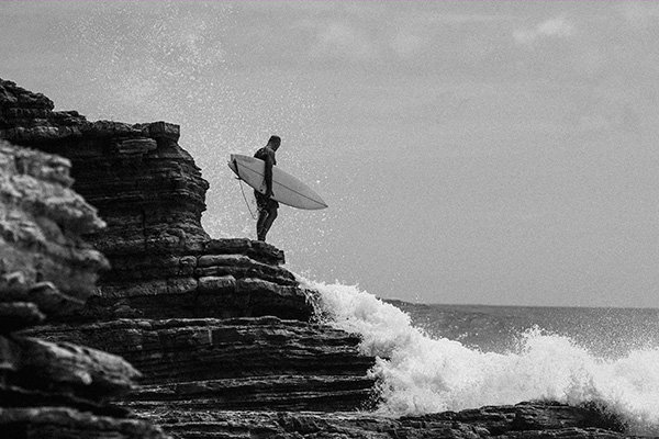 A black-and-white photograph shows Jeff Johnson holding a surfboard under his right arm while standing on a short cliff watching waves crash over the rocks.
