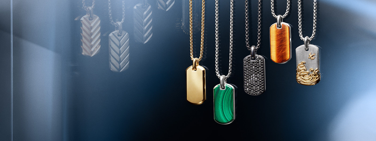 A color photograph shows a horizontal row of five David Yurman men's tags from the Streamline®, Exotic Stone, Pavé and Waves collections strung on box-chain necklaces and hanging in front of a reflective surface with angular, multi-colored reflections of light and jewelry. The Streamline® tag is crafted from 18K yellow gold and is strung on an 18K yellow gold chain. The Exotic Stone tags are crafted from sterling silver with inlaid malachite or tiger's eye, and are strung on sterling silver chains. The Pavé tag is crafted from black titanium with pavé black diamonds and is strung on a black titanium chain. The Waves tag is crafted from sterling silver with 18K yellow gold and is strung on a sterling silver chain.