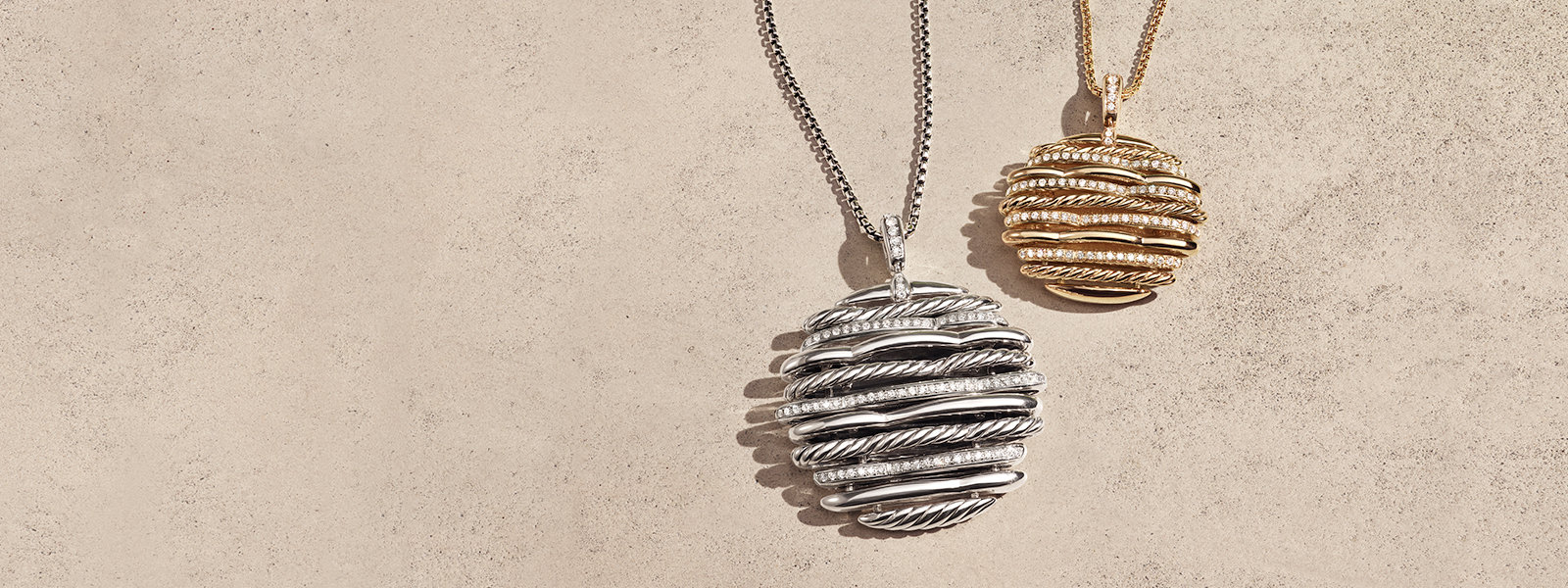 David Yurman Tides pendant necklaces in sterling silver or 18K yellow gold with white diamonds, next to one another and casting shadows on a light textured stone.