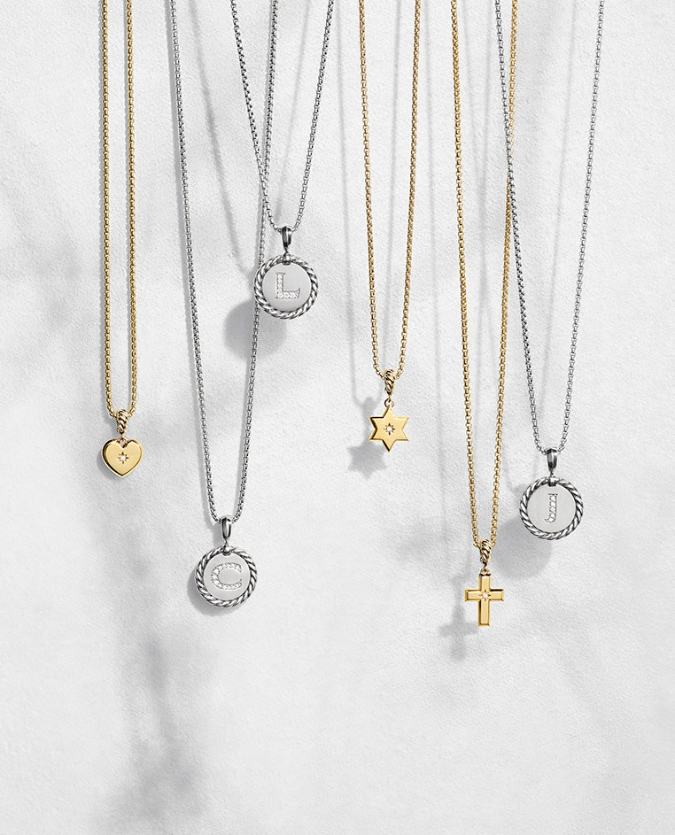 David Yurman necklaces in 18K yellow gold with a pavé diamond heart, star of diamond and cross pendant hanging next to Cable Collectibles® necklaces in sterling silver with pavé diamond initial charms—all shot against a white stone with long shadows.