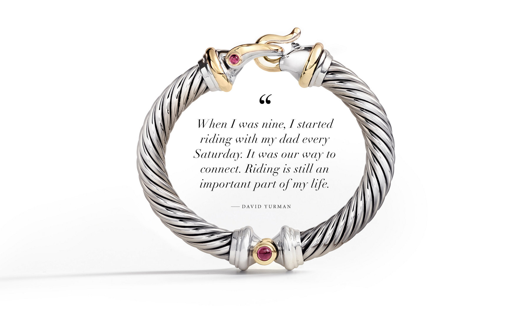 A quote by David Yurman placed in the space in the center of a sterling silver Cable bracelet with a buckle-shaped clasp, 18K yellow gold details and rhodalite garnet.