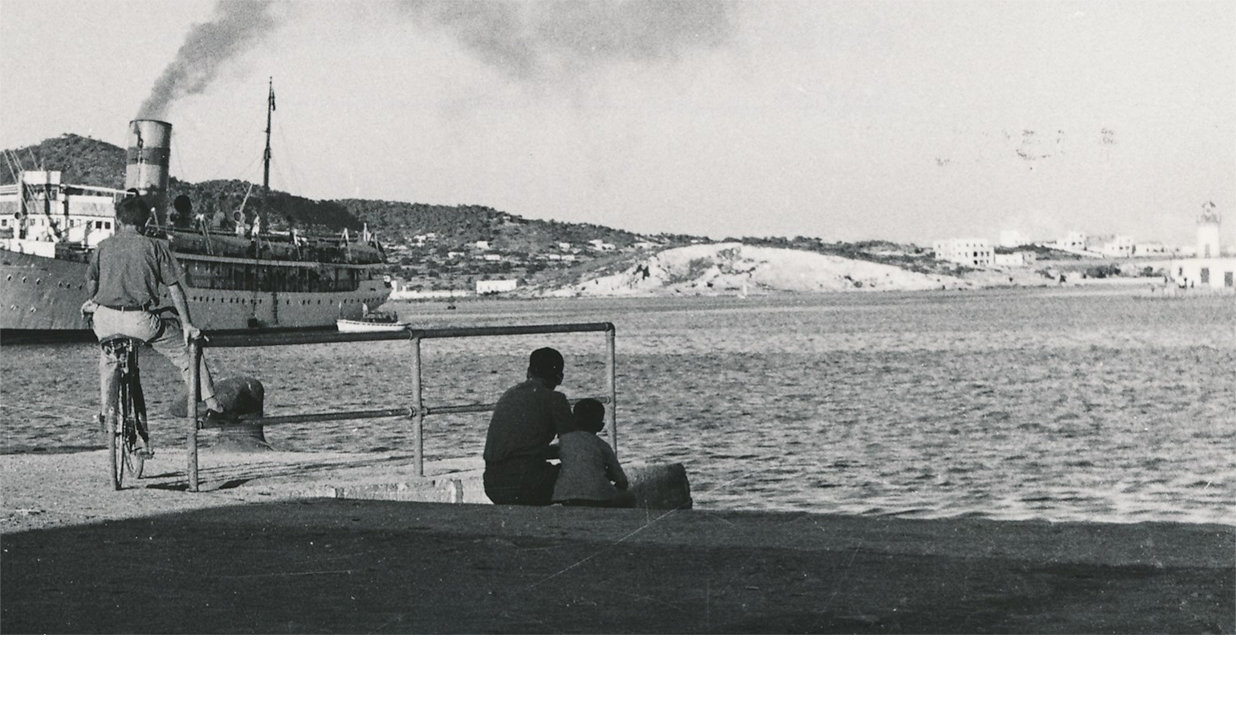 A black-and-white photo of the Port of Ibiza with a boat and people by the waterfront.