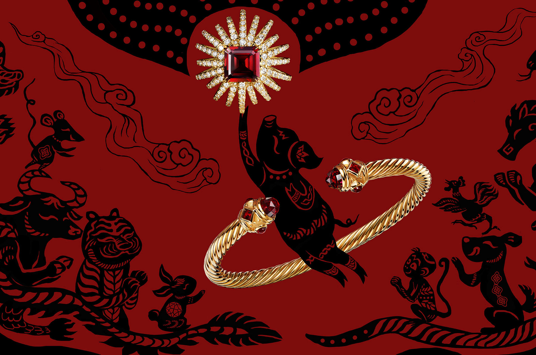 A red-and-black illustration with Chinese zodiac animals, including a pig. A David Yurman Starburst ring in 18K yellow gold with garnet and a Cable bracelet in 18K gold are placed on top of the illustration.