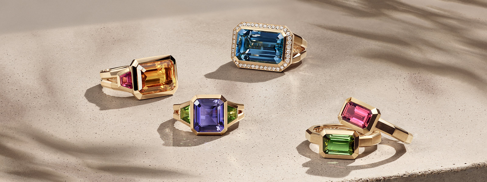 David Yurman Novella rings in 18K yellow gold with citrine and rhodalite garnet, iolite and green tourmaline, blue topaz and diamonds, or green or pink tourmaline, arranged in a group on a sandy-colored stone illuminated with the designs casting long shadows.