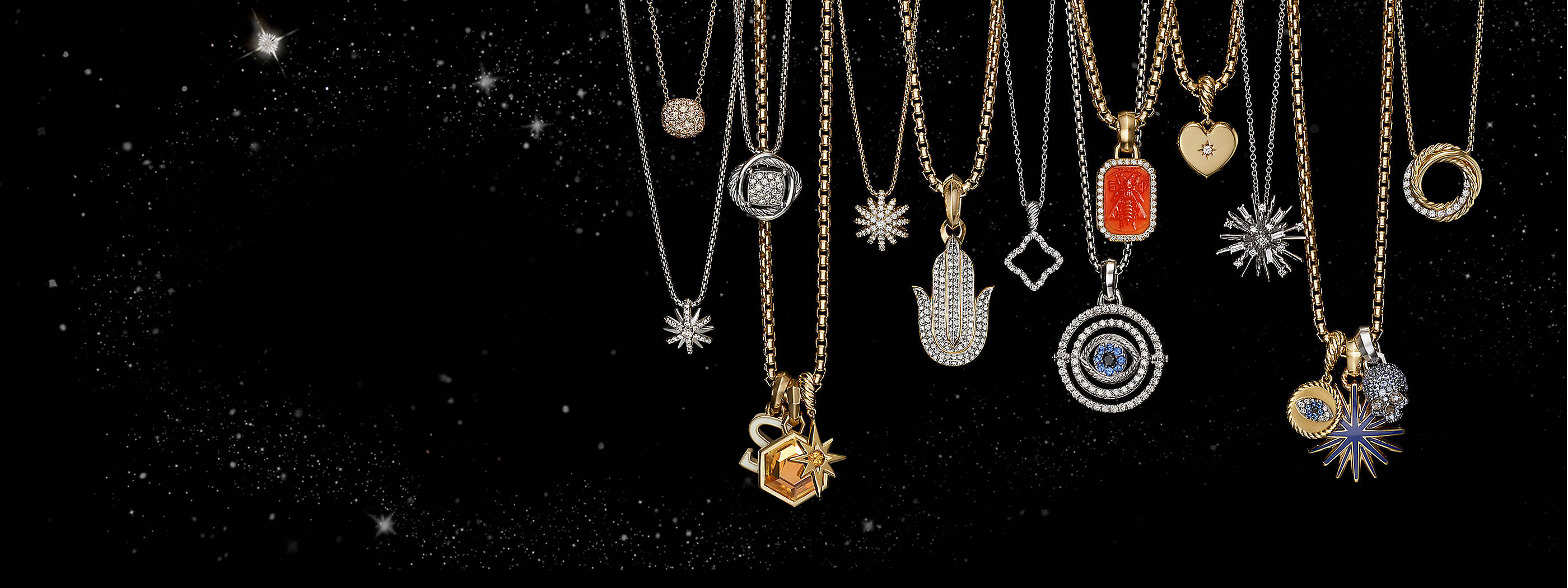 A color photo shows a horizontal row of 17 David Yurman women's amulets and pendants strung on 13 box chain necklaces hanging in front of a starry night sky. The women's jewelry is crafted from 18K yellow or white gold or sterling silver with or without diamonds or colored gemstones like citrine, sapphires or rubellite. The charms are shaped like stars, a skull, a hand, an octagon, the letter S or a heart, or depict an evil eye or bee