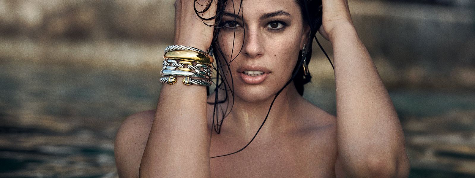 Model Ashley Graham half submerged in water wearing David Yurman Pure Form® bracelets in sterling silver and 18K yellow gold, and Wellesley Link™ and The Cable Collection bracelets in sterling silver with 18K yellow gold.