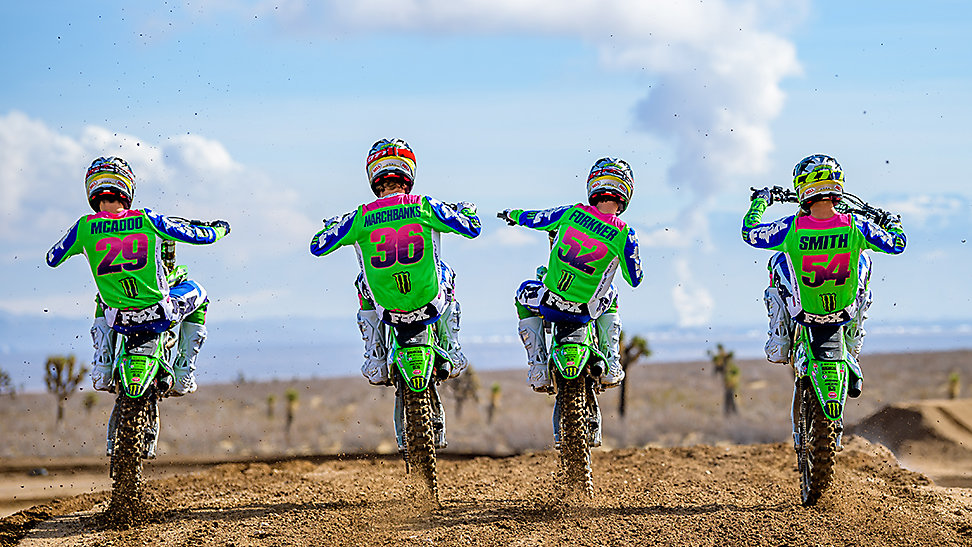 The four-person 2020 250SX Class Pro Circuit team doing side-by-side wheelies as they ride away from the camera.