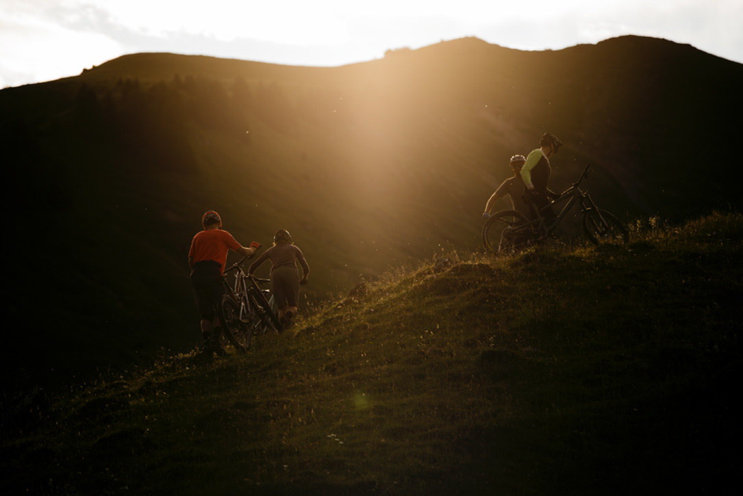 Mountain bikers riding was at dawn as the sun rises from behind mountains in the distance.