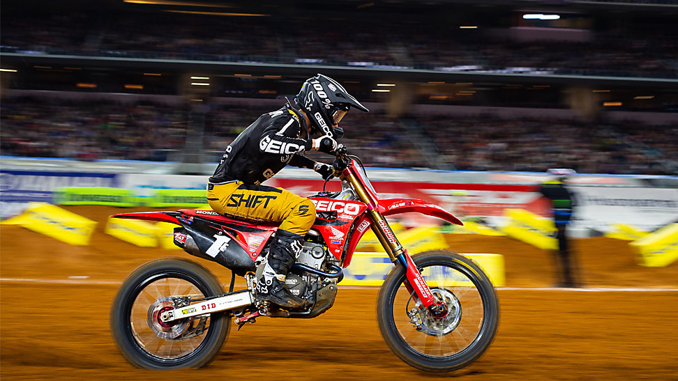 Chase Sexton racing left to right at the 2020 Arlington Supercross. The background has a motion blur.
