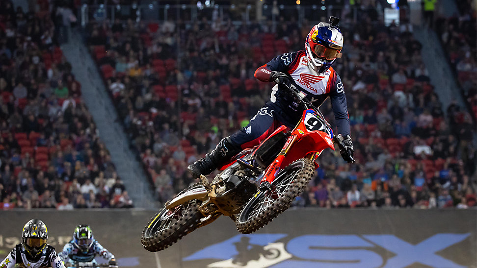450 Atlanta Supercross winner, Ken Roczen, jumping his dirt bike over a jump and leading the race.