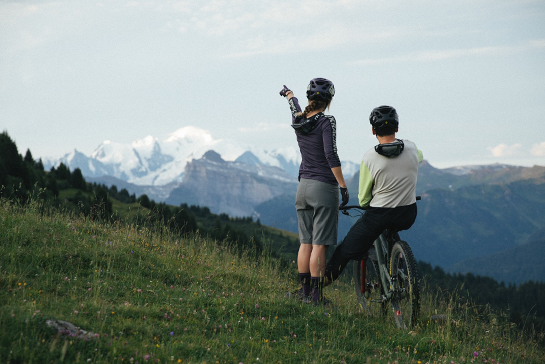 Two mountain biking standing on a green hill. One rider points off into the distance.