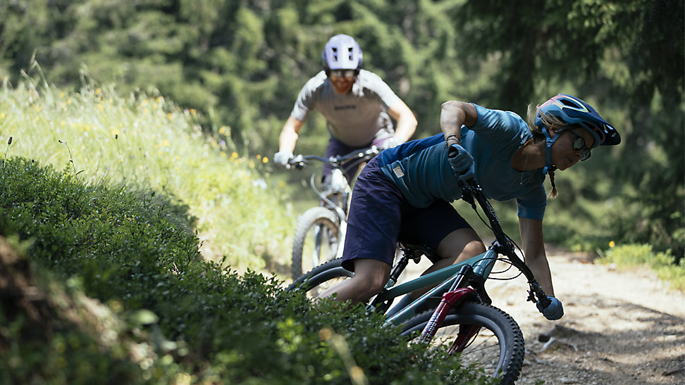 Two mountain bikers riding on a trail. Both are seen wearing the Fox Speedframe Pro Helmet