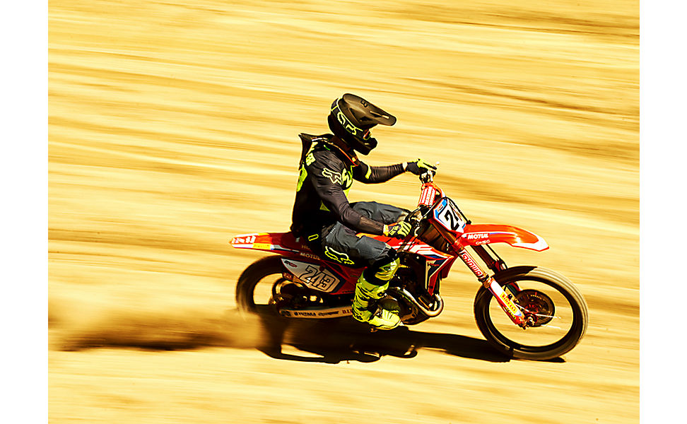 Tim Gajser rapidly racing his dirt bike, the background in motion blur. He is equipped in the MX20 racewear.