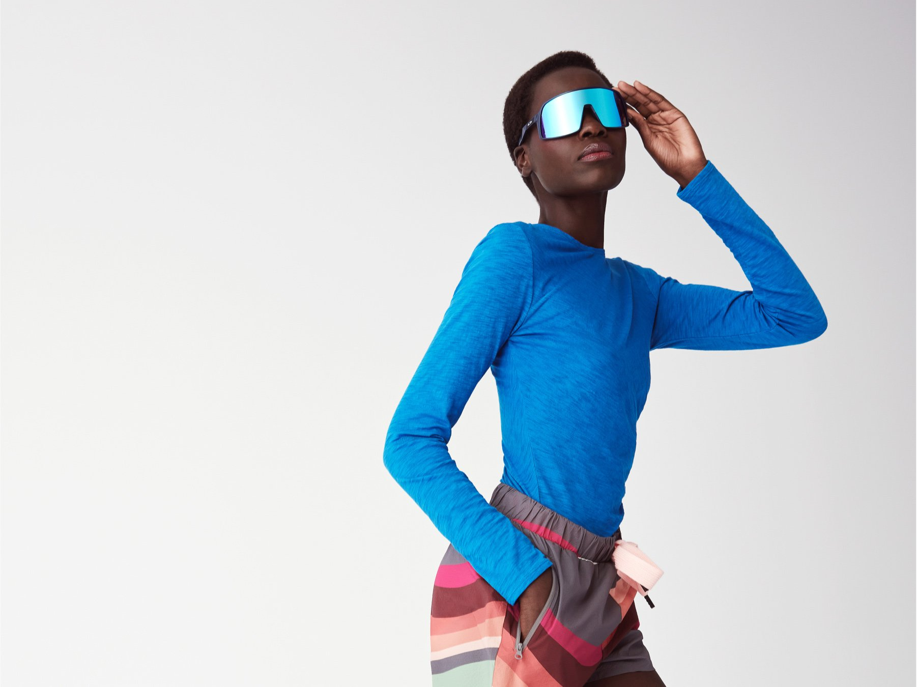 A Black female model with short hair runs in a bright blue long-sleeved tee and striped shorts.