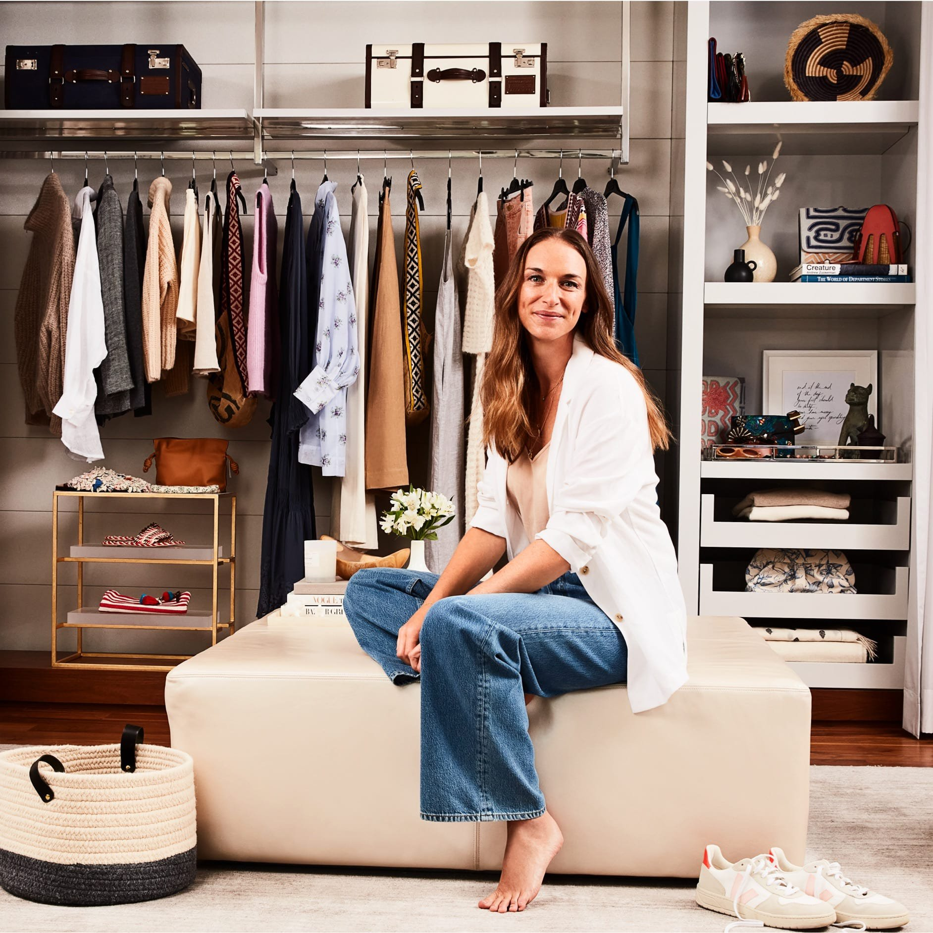 Alexandra Weston wears a white blazer and jeans while seated in front of a closet.