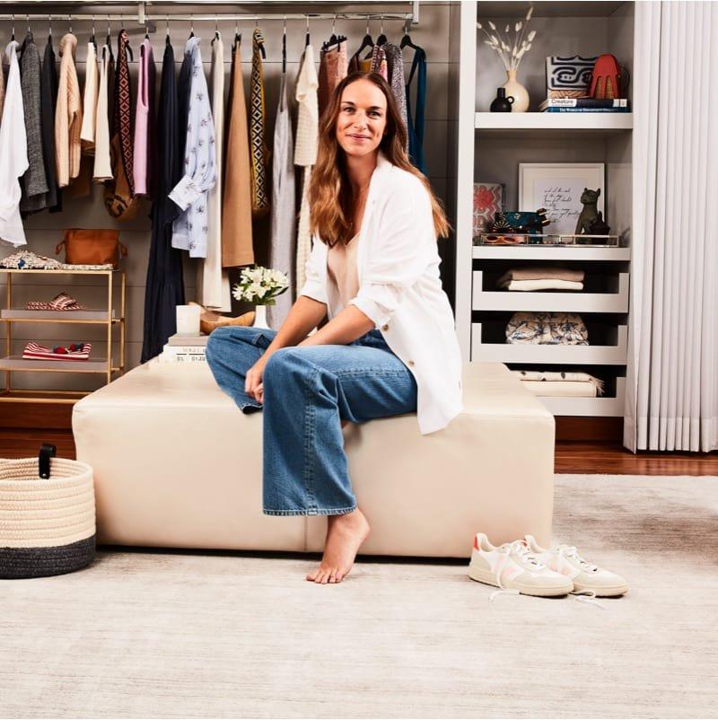 Alexandra Weston porte un blazer blanc et un jean assise devant sa garde-robe.