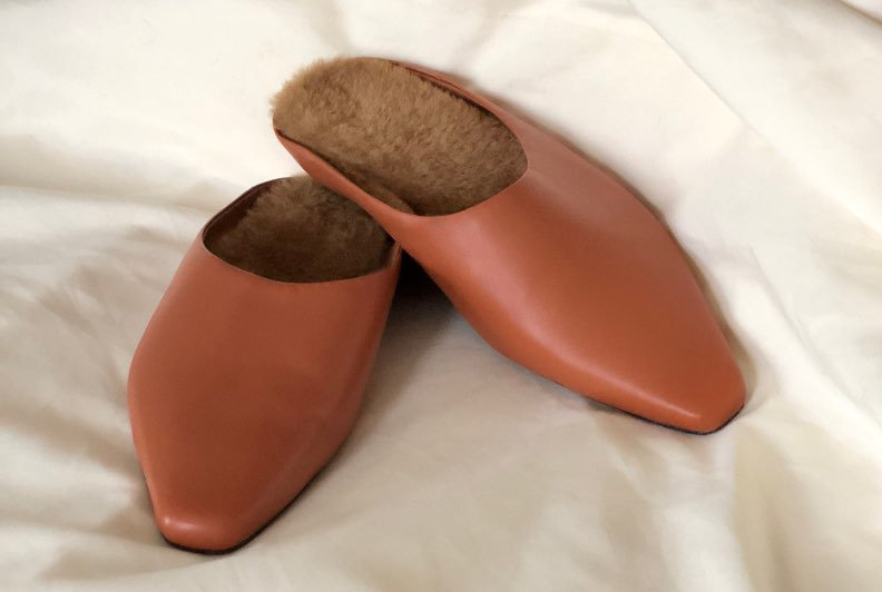 Light brown leather slides styled on top of cream bedsheets in a bedroom