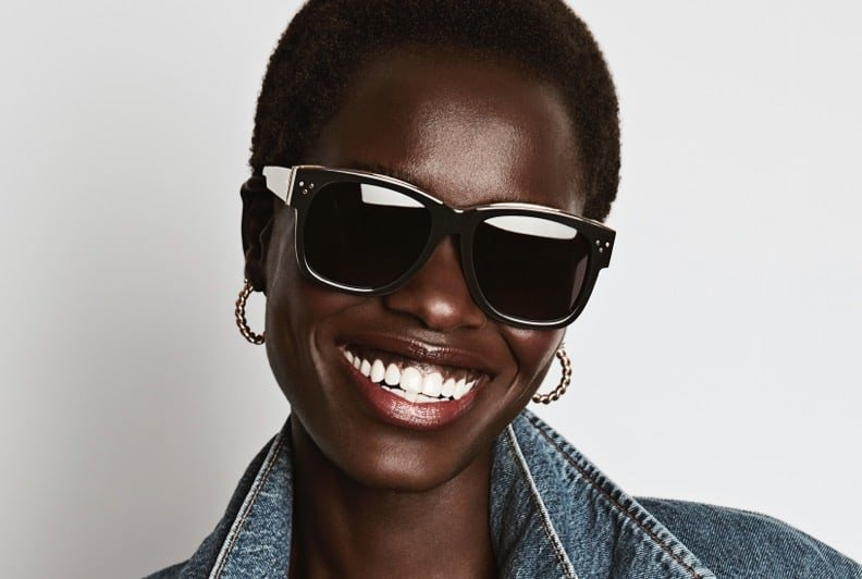 A female model wearing sunglasses, small hoop earring, and a denim jacket, with a big smile on her face