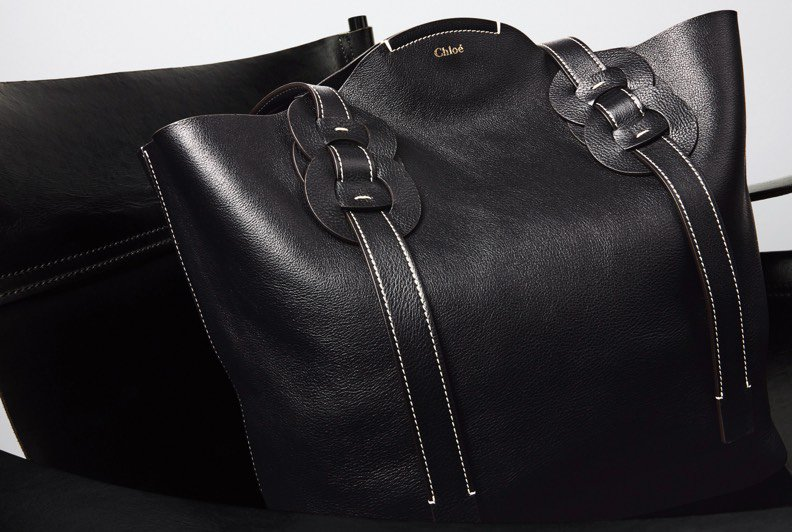 A black leataher tote with strap and buckle details on each side