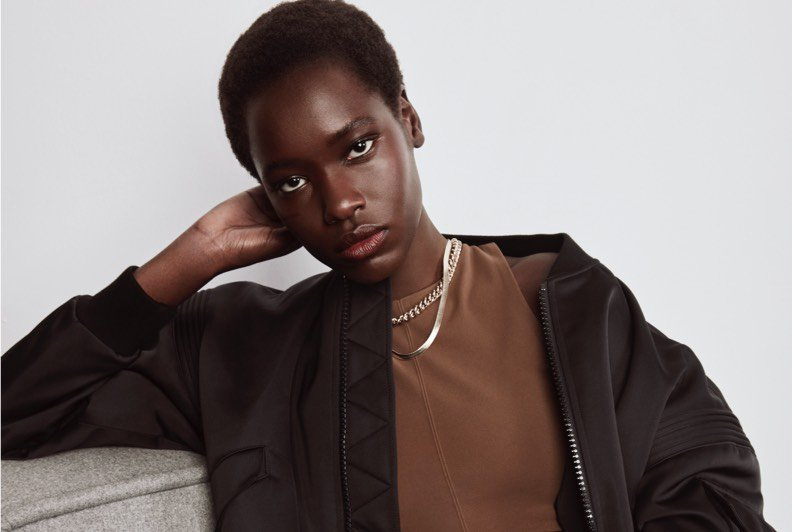 A model sitting on a couch wearing a bomber jacket, top, jeans, and two gold necklaces.