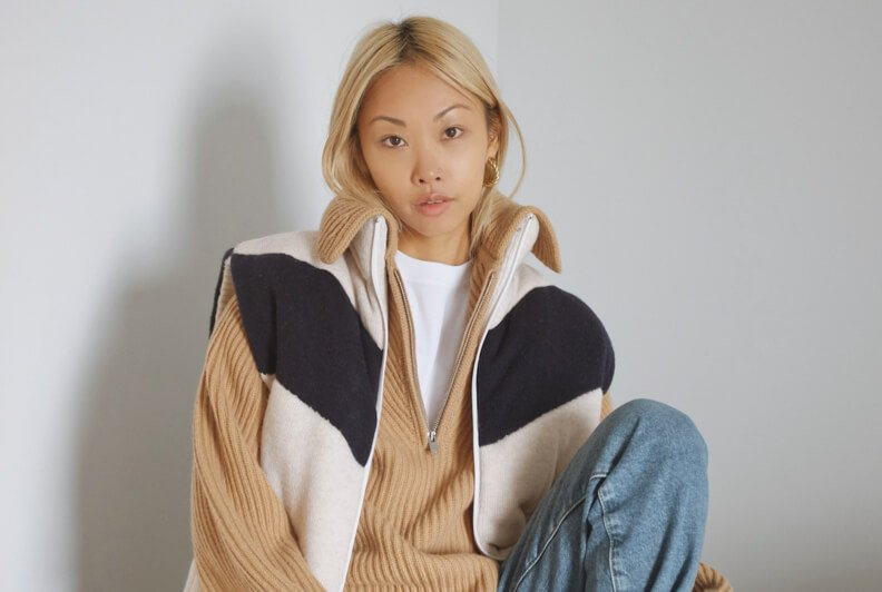 A woman sittig on a chair with one leg up, wearing a puffer vest, an oversized sweater, and ripped denim