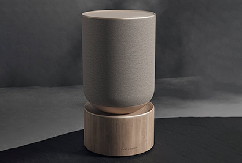 A sculptural speaker with a light wood base shot on a grey background