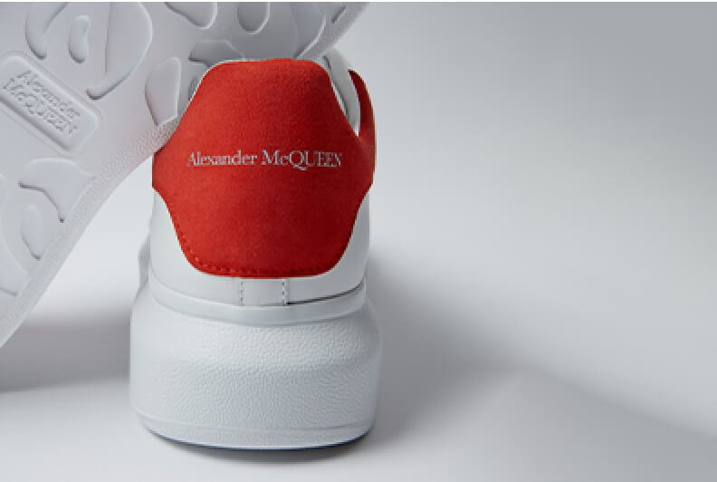 White sneaker with a chunky sole and a branded red tab on the heel.