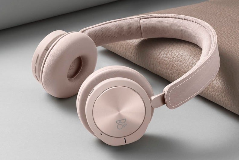 Soft pink over the ear headphones resting on their side against a piece of wood on a grey background