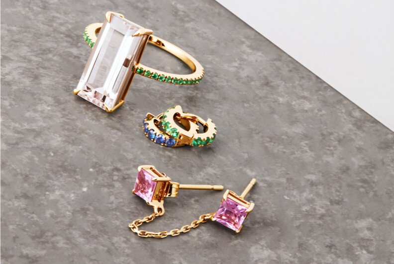 An off-figure shot of pieces of jewellery, a ring with a large rectangular gem and two sets of earrings