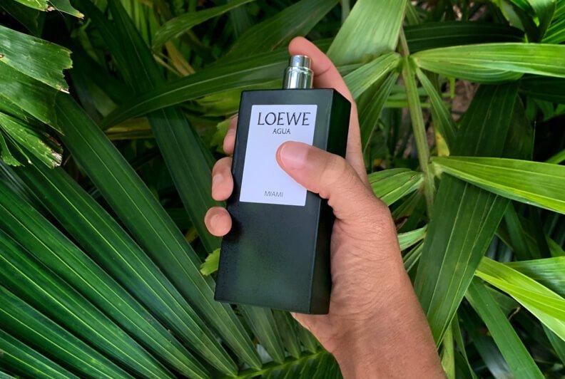 Main d'un homme tenant un flacon de parfum vert à étiquette blanche devant du feuillage luxuriant.