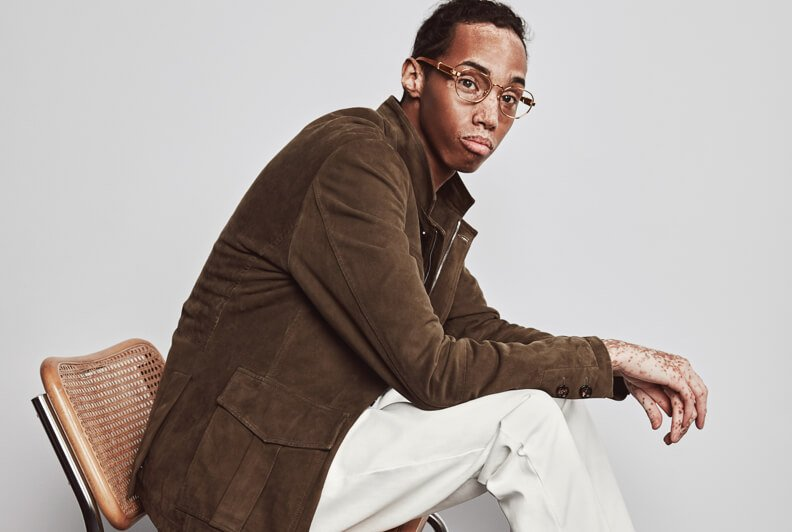A male model shot in profile sittin gon a chair, wearing a brown suede jacket, white pants, and white shoes.