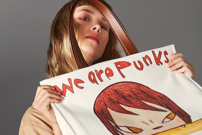 A White female model posing on a grey backdrop holding an oversized tote with an anime-style drawing of a face on the front.