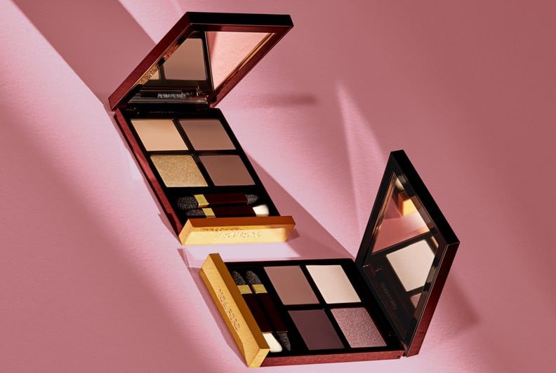 Two eyeshadow palettes open to reveal the makeup and mirror insides styled on a pink set.