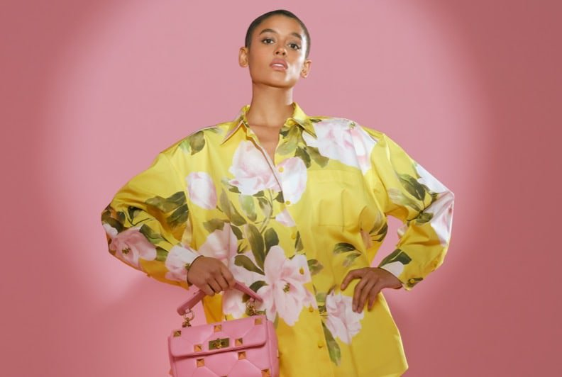 A Black woman with a shaved head posing on a pink set wearing a yellow floral print shirt dress, pink pumps, and holding a pink handbag.