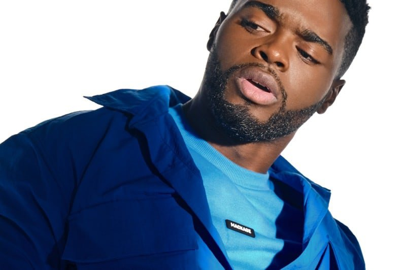 A Black male dancer posing on a white set and wearing a blue jacket over a blue shirt.