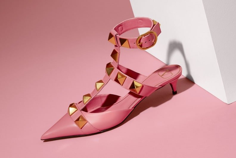 Pink ankle strap kitten heels with a pointy toe and gold studs styled on a pink and white set.Pink ankle strap kitten heels with a pointy toe and gold studs styled on a pink and white set.