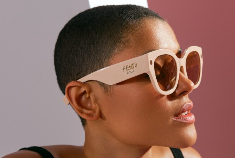A Black woman with a shaved head photographr in a close up wearing pink sunglasses and a black tank top.
