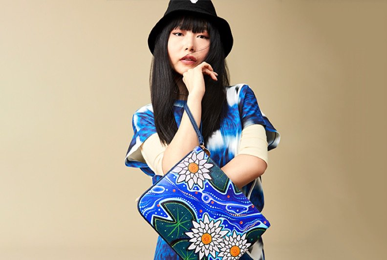 An Asian female model posting against a beige backdrop wearing a blue and white printed shirt and bucket hat, and holding a pouch that features water lily artwork