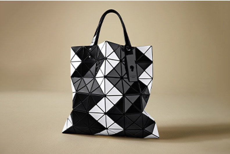 A white and black geometic Bao Bao Issey Miyake tote bag shot on a beige backgrund