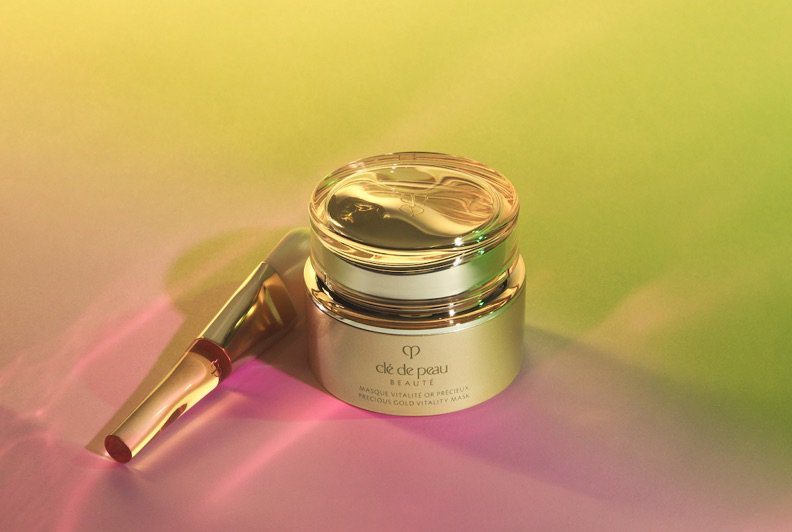 Two golden Clé de Peau beauty products on a gradient background of pink, green, and yellow