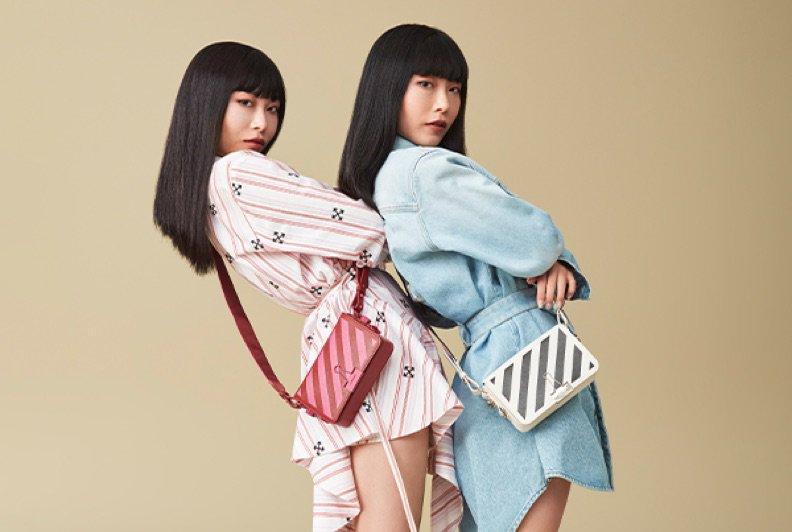 Mannequins jumelles portant robes chemisiers, chaussures colorées et sacs à bandoulière rayés.