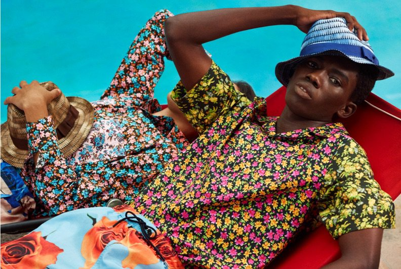 Two male models lounding poolside wearing printed shirts, shorts, and hats