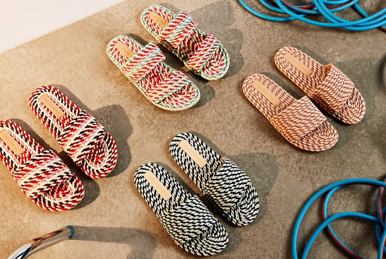 Four pairs of colourful woven sandals on a concreate floor surrounded by blue cables
